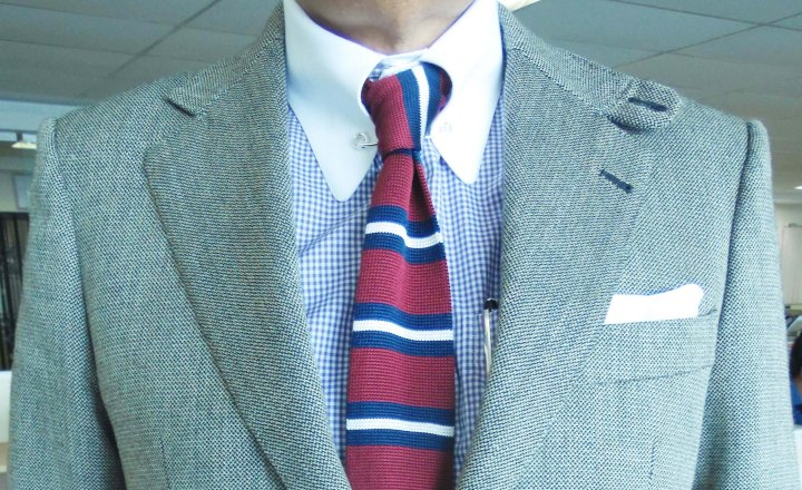 Gray sports jacket, blue micro-check contrast collar shirt, maroon/black/white striped silk knit tie, white linen pocket square