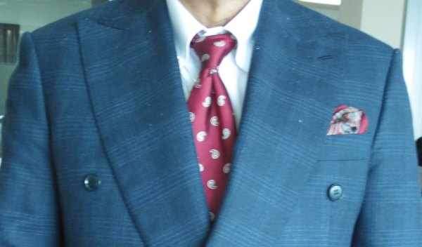 Blue check suit, maroon silk tie with paisley designs, maroon and blue printed silk pocket square