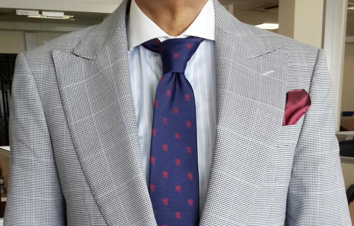 Light gray check suit, blue and white check contrast collar shirt, blue silk tie with maroon motifs, maroon silk pocket square