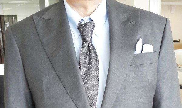 Gray suit, white shirt, brown printed silk tie, and  white linen pocket square