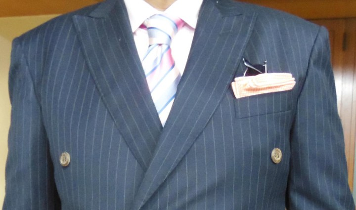 Gray pinstripe suit, light pink shirt, pink and blue striped silk tie, pink check pocket square