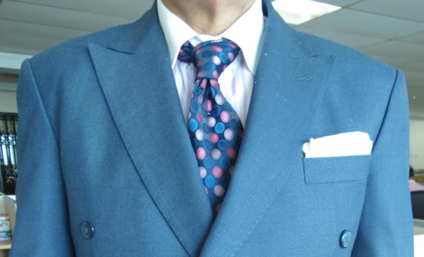 blue suit, white shirt, multi-colored tie, and white linen pocket square