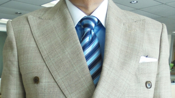 Light brown suit, blue contrast collar shirt, blue on blue striped silk tie, white linen pocket square