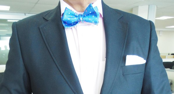 Blue subtle check suit, light pink shirt, blue and pink bow tie, light pink linen pocket square