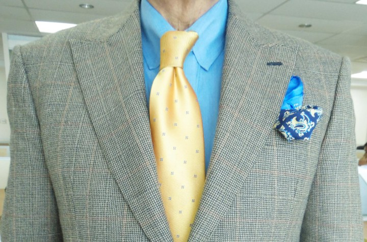 brown and blue check suit, blue shirt, yellow tie, blue and yellow printed silk pocket square