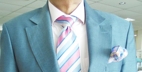Light blue suit, light pink shirt, pink and blue striped silk tie, pink and blue silk pocket square