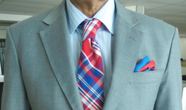 Light gray suit, blue and white striped shirt, red and blue tartan cotton tie, blue and red silk pocket square