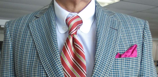 Check suit, reddish striped silk tie, reddish silk pocket square.