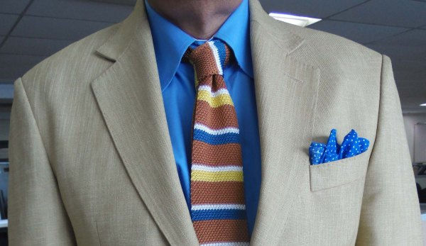 Light mustard suit, blue shirt, mustard/yellow/blue striped silk knit tie, blue and white linen pocket square