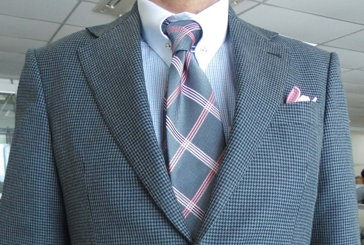 Gray hounds tooth suit, gray and pink check silk tie, pink and blue silk pocket square