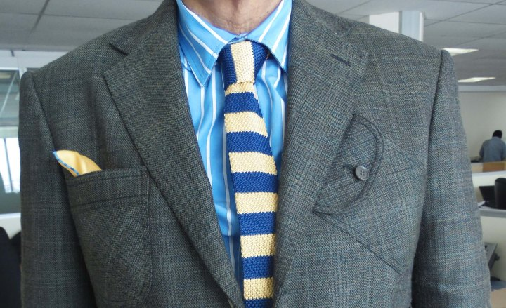 Gray check sports jacket, blue/white striped shirt, blue/yellow striped silk knit tie, yellow and blue pocket square