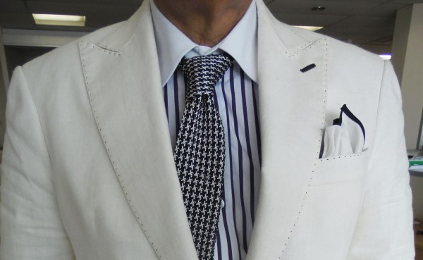 Cream linen sports jacket, blue/black striped contrast collar shirt, black/white silk knit tie, white linen pocket square with black border.