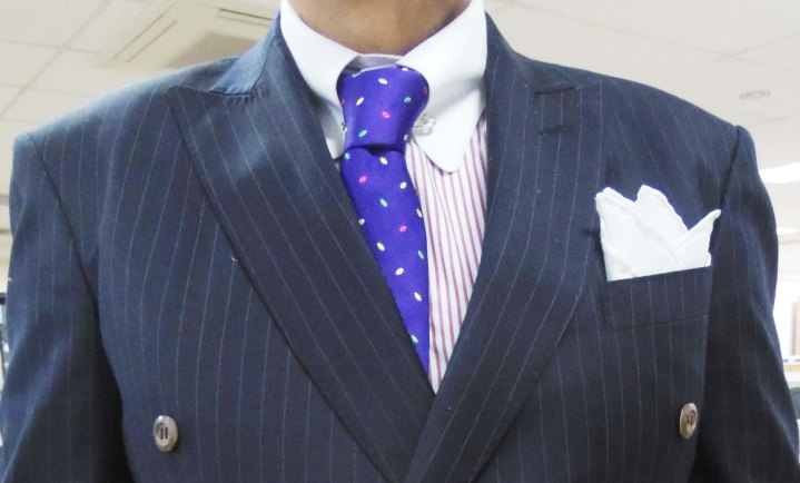 Gray pinstripe suit, contrast collar striped shirt, blue tie with green and red dots, white linen pocket square