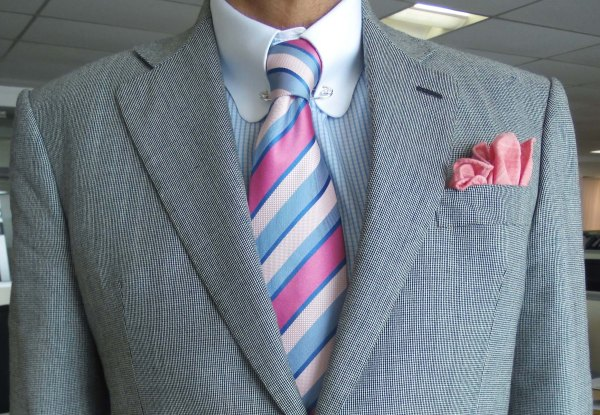 Mid gray suit, blue candy stripe contrast collar shirt, pink and blue striped silk tie, pink linen pocket square